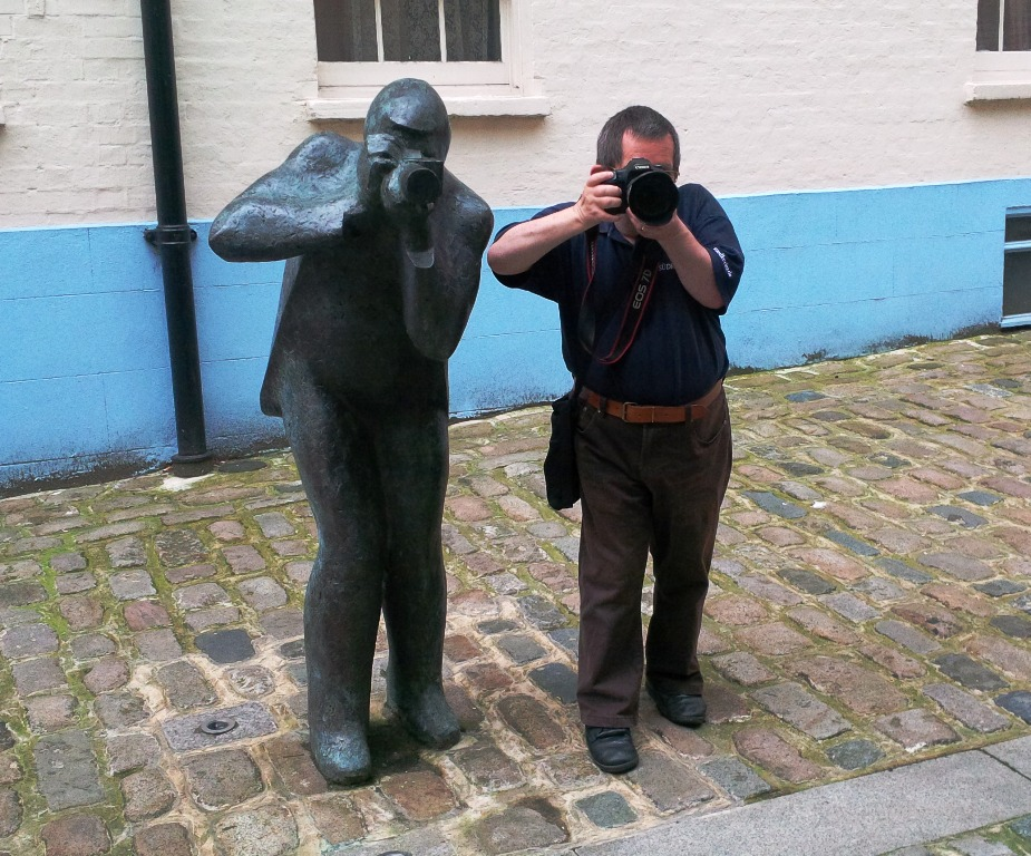 Fotograf (rechts) neben einer Fotografen-Statue (links)